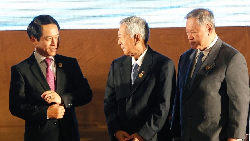 Laotian Foreign Minister Saleumxay Kommasith, left, talks to his counterpart Perfecto Yasay Jr. of the Philippines, center, and Brunei's Trade Minister Jock Seng Pehin Lim after the opening ceremony of the 49th Association of Southeast Asian Nations (ASEAN) Foreign Ministers' Meeting in Vientiane, Laos, Sunday, July 24, 2016. (AP Photo/Sakchai Lalit)