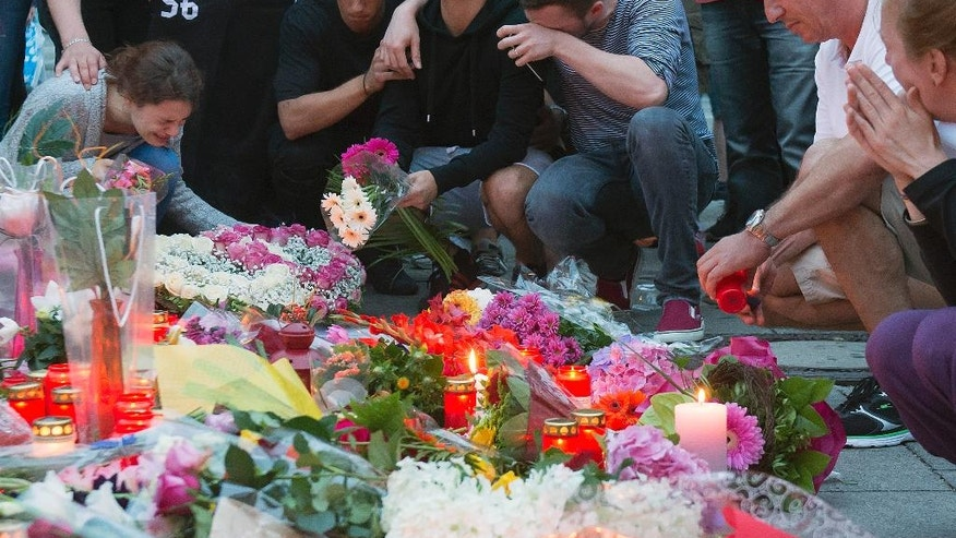 People mourn behind flower tributes near the Olympia shopping center where a shooting took place leaving nine people dead the day before, in Munich, Germany, Saturday, July 23, 2016. Police piecing together a profile of the gunman whose rampage at a Munich mall Friday left nine people dead described him Saturday as a lone, depression-plagued teenager. (AP Photo/Jens Meyer)