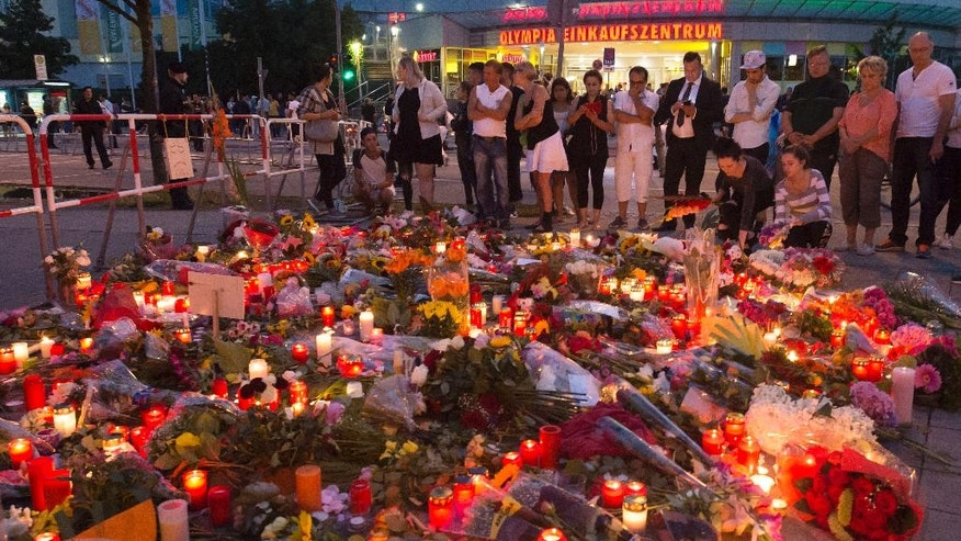 People gather to mourn with flower tributes near to the Olympia shopping center where a shooting took place leaving nine people dead the day before in Munich, Germany, Saturday, July 23, 2016. Police piecing together a profile of the gunman whose rampage at a Munich mall Friday left nine people dead described him Saturday as a lone, depression-plagued teenager.  (AP Photo/Jens Meyer)