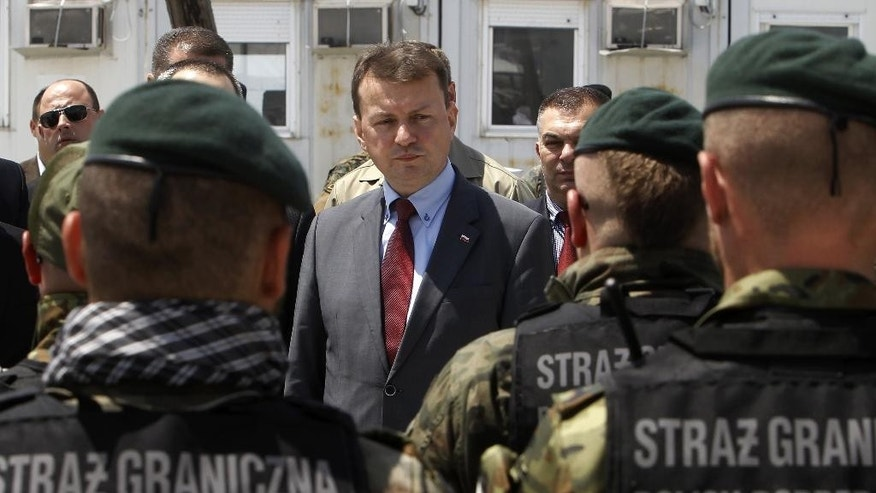 FILE- In this file photo dated Tuesday, May 24, 2016, Poland's Interior Minister Mariusz Blaszczak, centre, talks to Polish Border Guard officers deployed to help deal with migrants, at the refugee transit center near southern Macedonian town of Gevgelija.  Pope Francis begins a five-day visit to Poland on upcoming Wednesday and hopes to inspire aid to homeless strangers and acts of mercy for refugees, but Blaszczak argues that violence is an inevitable consequence of multiculturalism, and Poland could avoid such bloodshed by barring Muslims in particular. (AP Photo/Boris Grdanoski, FILE)