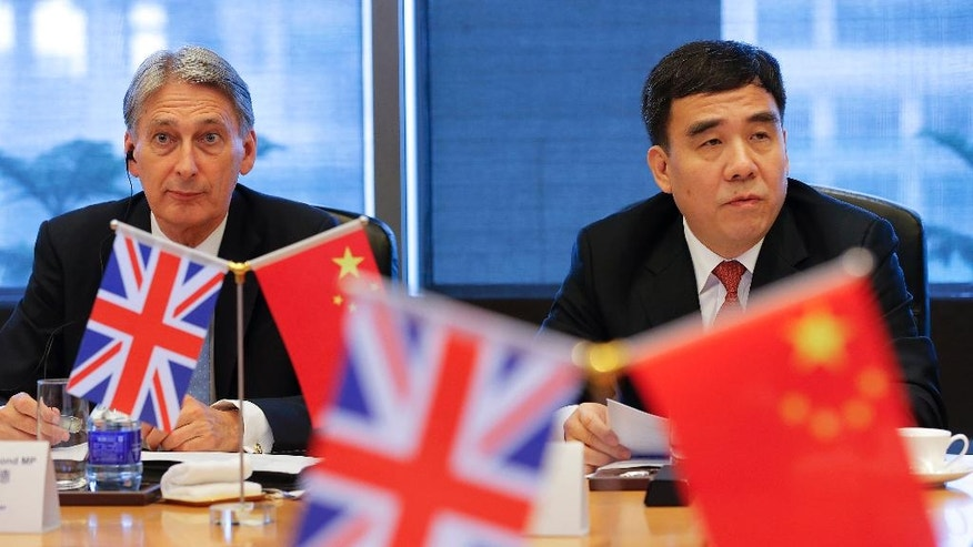 Britain's Chancellor of the Exchequer Philip Hammond, left, and Bank of China Chairman Tian Guoli attend UK-China High Level Financial Services Roundtable at the Bank of China head office building in Beijing Friday, July 22, 2016. (Damir Sagolj/Pool Photo via AP)