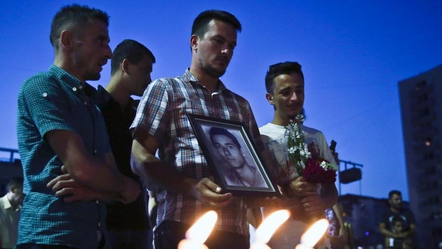 Relatives holding the picture of Diamond Zabergja, 21, gather in Kosovo's capital Pristina on Sunday, July 24, 2016, in vigil for the victims of the Olympia shopping centre in Munich, where a shooting took place leaving nine people dead two days ago. Three ethnic Albanians, two women and a man, were among the nine people killed by a gunman in Munich. (AP Photo/Visar Kryeziu)