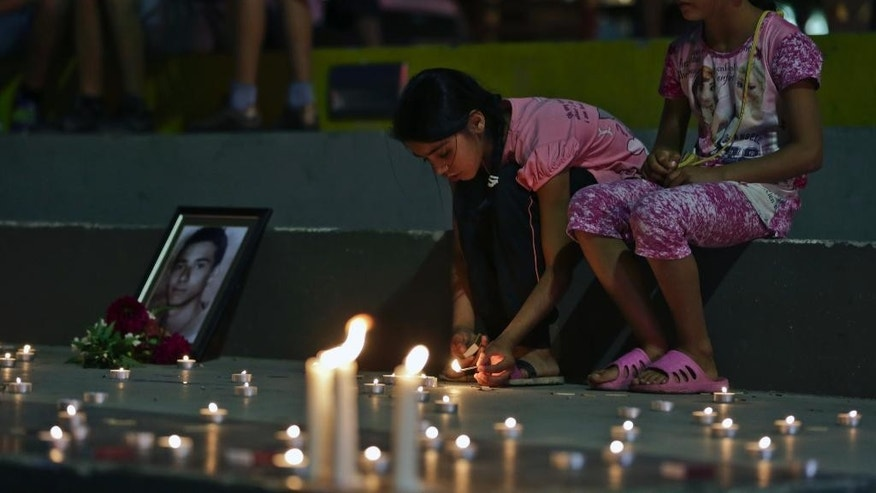 Two girls light candles in Kosovo's capital Pristina on Sunday, July 24, 2016, in vigil for the victims of the Olympia shopping centre in Munich, where a shooting took place leaving nine people dead two days ago. Three ethnic Albanians, two women and a man, were among the nine people killed by a gunman in Munich. (AP Photo/Visar Kryeziu)