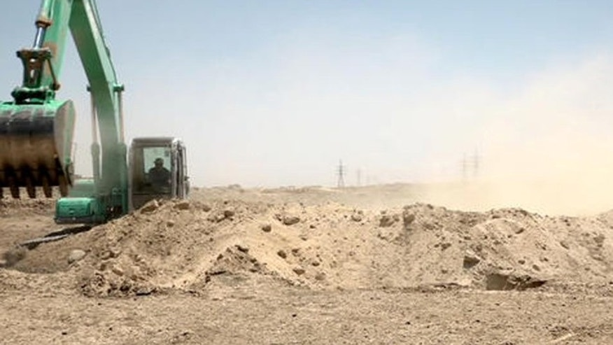 In this image made from video on Friday, July 22, 2016, a worker digs a trench on the outskirts of Fallujah, Iraq.