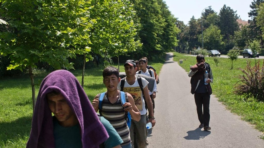 Migrants march by the side of a road in the town of Indjija, some 40 kilometers (24 miles) northwest of Belgrade, Serbia, Saturday, July 23, 2016. Hundreds of migrants and asylum seekers set off on foot Friday toward Serbia's border with Hungary to protest its decision to keep its border closed for most people trying to reach the European Union.  (AP Photo/Marko Drobnjakovic)