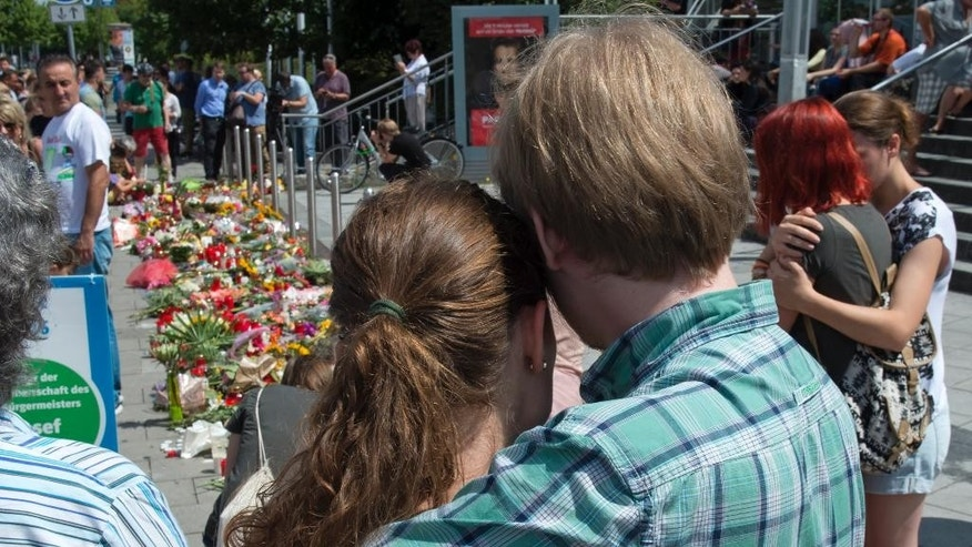 People mourn beside the Olympia shopping center where a shooting took place leaving nine people dead two days ago in Munich, Germany, Sunday, July 24, 2016. (AP Photo/Jens Meyer)