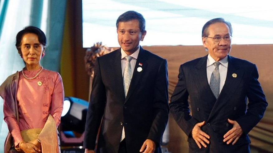 From left to right, Myanmar Foreign Minister Aung San Suu Kyi, Singapore's Foreign Minister Vivian Balakrishnan, Thai Foreign Minister Don Pramudwinai pose for a group photo during an opening ceremony of the Association of Southeast Asian Nations (ASEAN) Foreign Ministers' Meeting in Vientiane, Laos, Sunday, July 24, 2016. Southeast Asia's main grouping opened a meeting of their foreign ministers Sunday, deeply divided on how to deal with China's territorial expansion in the South China Sea that has impacted some of its members and whipped up an increasing diplomatic quagmire. (AP Photo/Sakchai Lalit)