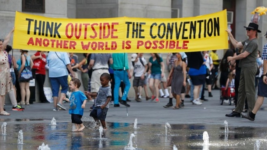 Demonstrators carry a sign around Dillworth Park as two youngsters play in the fountain on Sunday, July 24, 2016, in Philadelphia. The Democratic National Convention starts Monday in Philadelphia. (AP Photo/Alex Brandon)