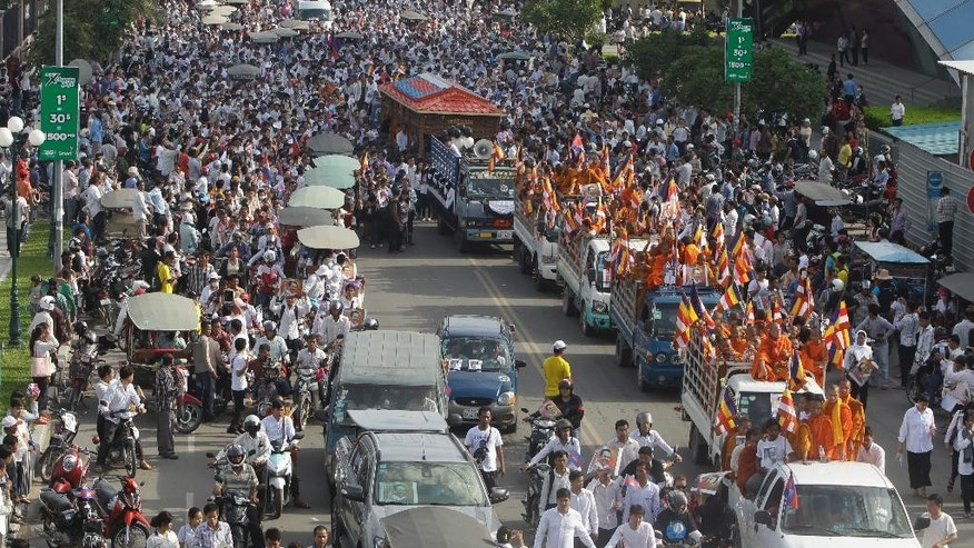 Cambodian mourners follow the body of Cambodian leading government critic Kem Ley in a glass casket carried on a decorated vehicle, top, on the main street during a funeral procession at Chroy Changvar in Phnom Penh, Cambodia, Sunday, July 24, 2016. Tens of thousands of Cambodians marched Sunday in the funeral procession for Kem Ley who was fatally shot in an attack that raised suspicion of a political conspiracy. (AP Photo/Heng Sinith)