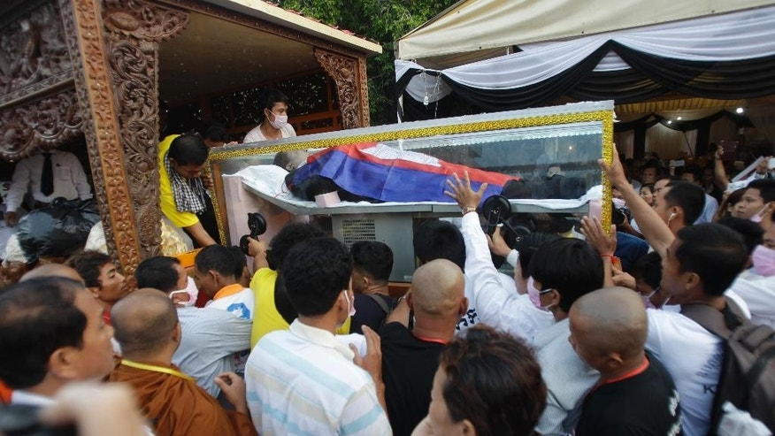The body of Cambodia's prominent political analyst Kem Ley placed in a glass casket is loaded on a decorated vehicle for the funeral procession at Chroy Changvar in Phnom Penh, Cambodia, Sunday, July 24, 2016. Tens of thousands of Cambodians marched Sunday, in the funeral procession for the leading government critic who was fatally shot in an attack that raised suspicion of a political conspiracy. (AP Photo/Heng Sinith)