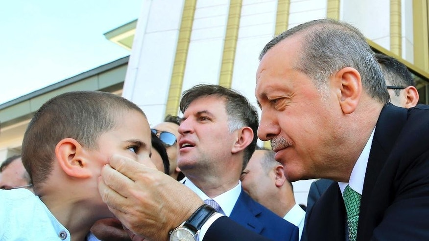 In this Friday, July 22, 2016 photo, Turkey's President Recep Tayyip Erdogan, right, pinches a child's cheeks, following Friday prayers at a mosque, in Ankara, Turkey. Turkish lawmakers approved a three-month state of emergency that allows the government to extend detention times and issue decrees without parliamentary approval.(Press Presidency Press Service via AP, Pool)