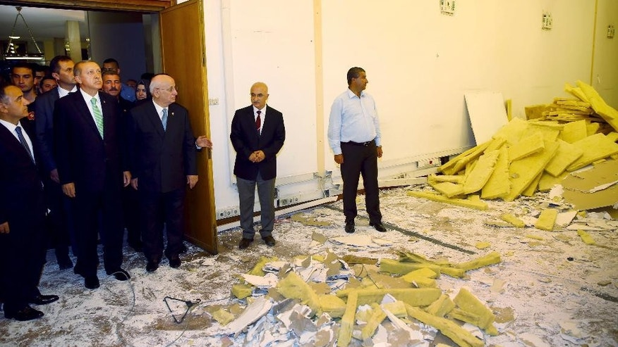 In this Friday, July 22, 2016 photo, Turkey's President Recep Tayyip Erdogan, 2nd left, inspects the damage from the fighting during the July 15 attempted coup at the parliament in Ankara, Turkey. Turkish lawmakers approved a three-month state of emergency that allows the government to extend detention times and issue decrees without parliamentary approval. (Press Presidency Press Service via AP, Pool)