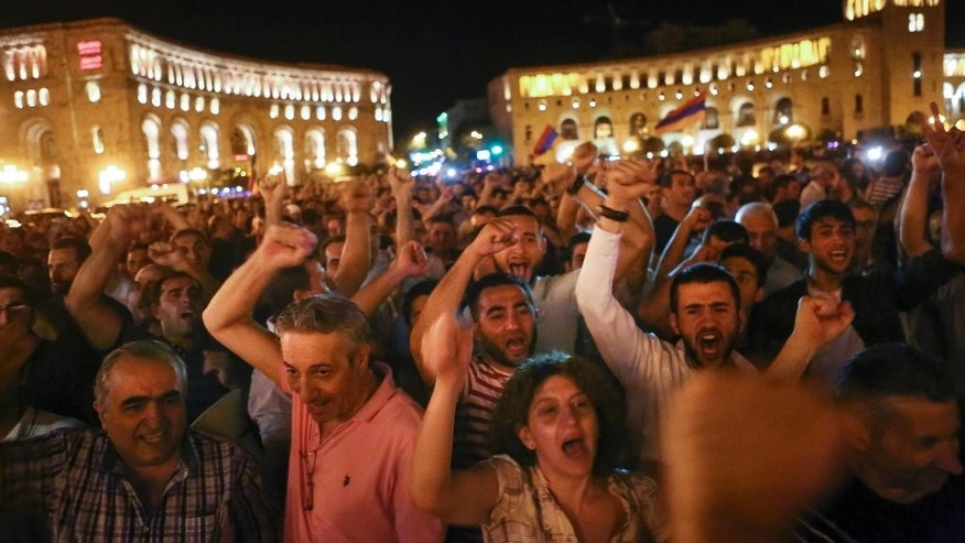Protesters shout as they gather at Republic Square in Yerevan, Armenia, Monday, July 25, 2016. Authorities say the gunmen who have held a police station in the Armenian capital for nine days to demand the release of an opposition figure who was arrested last month, have set a police vehicle on fire as a crowd of about 2,000 people gathered at the standoff site. (Hrant Khachatryan/PAN Photo via AP)