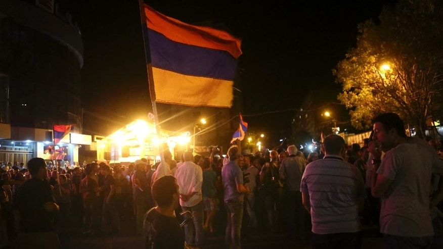 Protesters with an Armenian national flag gather at a police cordon near a police station in Yerevan, Armenia, Monday, July 25, 2016. Authorities say the gunmen who have held a police station in the Armenian capital for nine days to demand the release of an opposition figure who was arrested last month, have set a police vehicle on fire as a crowd of about 2,000 people gathered at the standoff site. (Hrant Khachatryan/PAN Photo via AP)