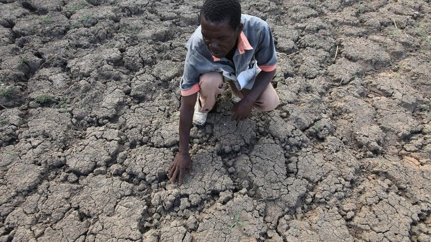FILE - In this file photo taken Sunday Jan. 29, 2016, Last Zimaniwa feels the broken ground at a spot which is usually a reliable water source that has dried up due to lack of rains in the village of Chivi , Zimbabwe. The United States on Monday July 25, 2016 announced $127 million in aid for southern African countries where the worst drought in decades is affecting millions of people. (AP Photo/Tsvangirayi Mukwazhi, File)