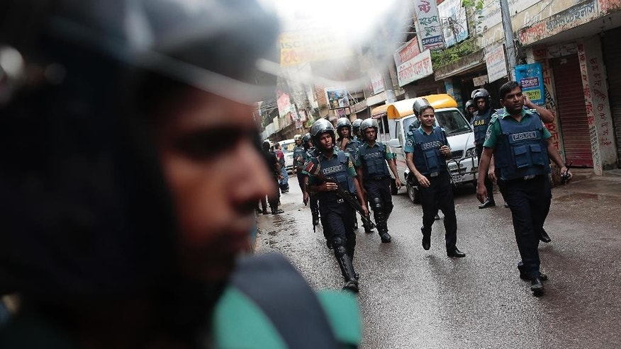 Policemen return after raiding a building in Dhaka, Bangladesh, Tuesday, July 26, 2016. Police in Bangladesh's capital raided a five-story building Tuesday and killed nine suspected Islamic militants the country's police chief said. (AP Photo/A.M. Ahad)
