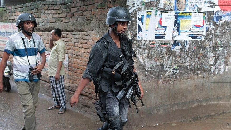 Policemen return after the raiding a building in Dhaka, Bangladesh, Tuesday, July 26, 2016. Police in Bangladesh's capital raided a five-story building Tuesday and killed nine suspected Islamic militants the country's police chief said. (AP Photo/A.M. Ahad)