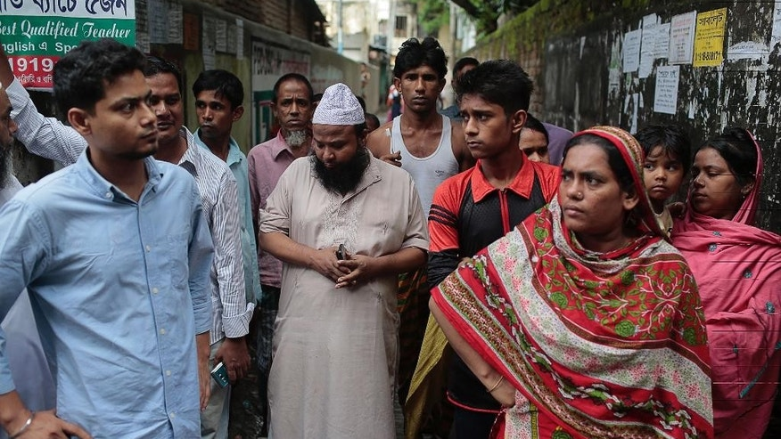 Locals look at the building where police killed suspected Islamic militants in Dhaka, Bangladesh, Tuesday, July 26, 2016. Police in Bangladesh's capital raided a five-story building Tuesday and killed suspected Islamic militants the country's police chief said. (AP Photo/A.M. Ahad)