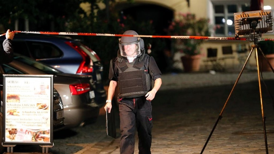 A special police officer leaves the area where an explosion occurred in Ansbach, Germany, Monday, July 25, 2016. Bavaria's top security official says a man who blew himself up after being turned away from an open-air music festival in the southern German city was a 27-year-old Syrian who had been denied asylum. (AP Photo/Matthias Schrader)