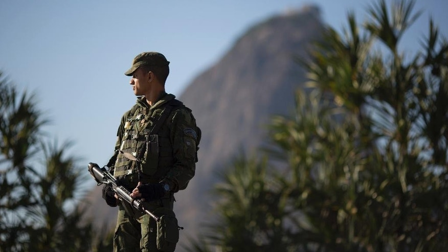 With Sugar Loaf mountain in the background a soldier patrols near Botafogo beach in Rio de Janeiro, Brazil, Sunday, July 24, 2016. Security has emerged as the top concern during the Olympics, that will kickoff on Aug. 5. (AP Photo/Leo Correa)