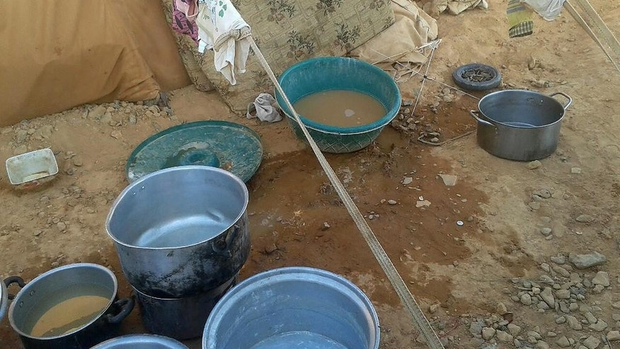 In this Sunday, July 10, 2016 photo, pots for water gather dust at the Ruqban border camp in northeast Jordan. A senior aid official says U.N. agencies have procured cranes to hoist food over an earthen barrier to tens of thousands of Syrians stranded on the border with Jordan, but are still waiting for Jordan's promised go-ahead. (AP Photo)