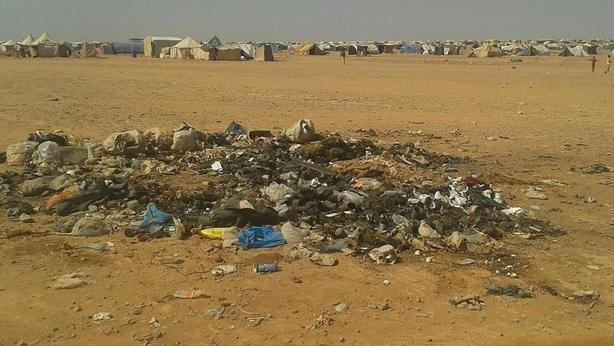 In this Sunday, July 10, 2016 photo, trash bakes in the sun from 64,000 Syrian refugees stranded in the Ruqban border camp in northeast Jordan. A senior aid official says U.N. agencies have procured cranes to hoist food over an earthen barrier to tens of thousands of Syrians stranded on the border with Jordan, but are still waiting for Jordan's promised go-ahead. (AP Photo)