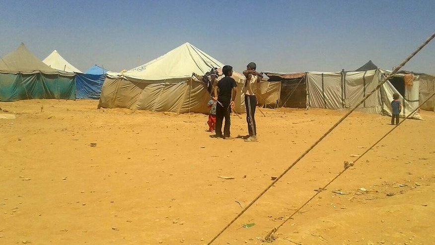 In this Sunday, July 10, 2016 photo, boys stand at the Ruqban border camp in northeast Jordan. A senior aid official says U.N. agencies have procured cranes to hoist food over an earthen barrier to tens of thousands of Syrians stranded on the border with Jordan, but are still waiting for Jordan's promised go-ahead. (AP Photo)