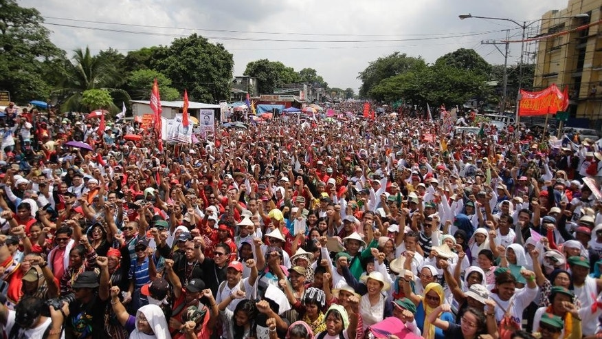 Filipino activists and supporters for Philippine President Rodrigo Duterte raise their clenched fists as they arrive near the gates of the House of Representative where President Duterte is set to deliver his first state of the nation address in suburban Quezon city, north of Manila, Philippines on Monday July 25, 2016. Thousands of activists were allowed near the gates to listen to President Duterte's speech. (AP Photo/Aaron Favila)