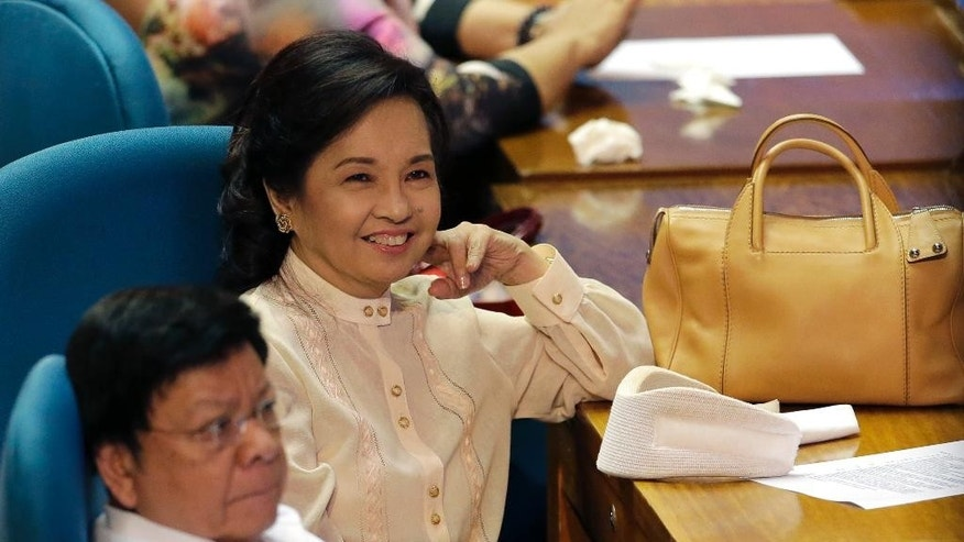 Former President and now Congresswoman Gloria Macapagal Arroyo smiles beside her neck brace during the opening session of the Philippine Congress where President Rodrigo Duterte is set to deliver his first state of the nation address at at the House of Representatives in suburban Quezon city north of Manila, Philippines on Monday, July 25, 2016. The Supreme Court ordered the immediate release of Arroyo last week after dismissing plunder charges against her. Arroyo was under hospital arrest for more than four years. (AP Photo/Aaron Favila)