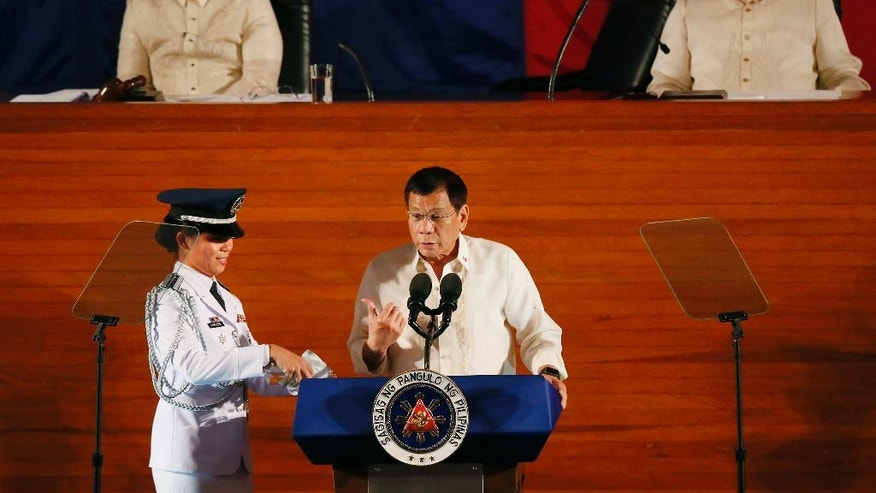 "Philippine President Rodrigo Duterte, gestures to his aide who pours drinking water while delivering his first State of the Nation Address (SONA) before the joint session of the 17th Congress Monday, July 25, 2016 , at suburban Quezon city northeast of Manila, Philippines. Listening at left is Senate President Aquilino ""Koko"" Pimentel and at right is House Speaker Pantaleon Alvarez. (AP Photo/Bullit Marquez)"