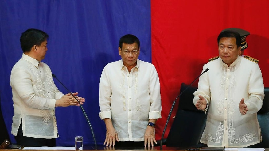 "Philippine President Rodrigo Duterte, center, is applauded by Senate President Aquilino ""Koko"" Pimentel, left, and House Speaker Pantaleon Alvarez prior to delivering his first State of the Nation Address (SONA) before the joint session of the 17th Congress Monday, July 25, 2016, at suburban Quezon city northeast of Manila, Philippines. (AP Photo/Bullit Marquez)"