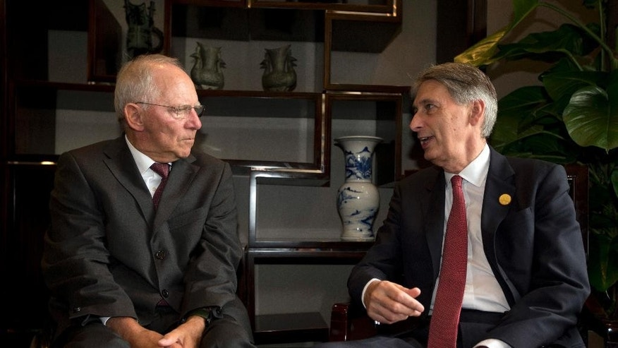 Britain's Chancellor of the Exchequer Philip Hammond, right, chats with Germany's Federal Minister of Finance Wolfgang Schauble before a private lunch on the sidelines of the G20 High-level Tax Symposium held in Chengdu in Southwestern China's Sichuan province, Saturday, July 23, 2016. Finance ministers and Central Bank governors of the 20 most developed economies are to meet in the southwestern city of Chengdu ahead of a G20 leaders meeting in September hosted by China. (AP Photo/Ng Han Guan, Pool)