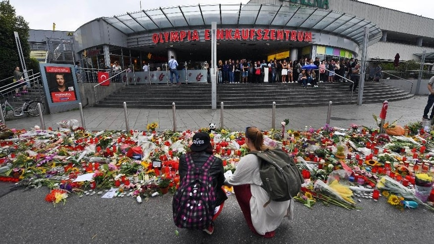 Flowers and candles have been placed in front of the main entrance of the Olympia-Einkaufszentrum (Olympia Shopping Mall) in Munich, Germany, Monday, July 25, 2016, after a rampage that left numerous people dead and injured. (Peter Kneffel/dpa via AP)