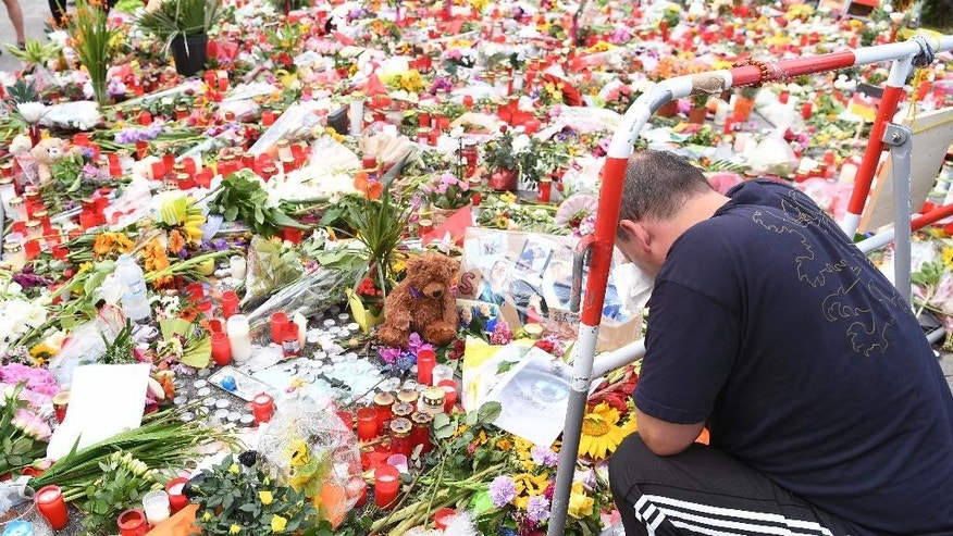 A man prays next to flowers and candles that have been placed in front of the main entrance of the Olympia-Einkaufszentrum (Olympia Shopping Mall) in Munich, Germany, Monday, July 25, 2016, after a rampage that left numerous people dead and injured. (Peter Kneffel/dpa via AP)