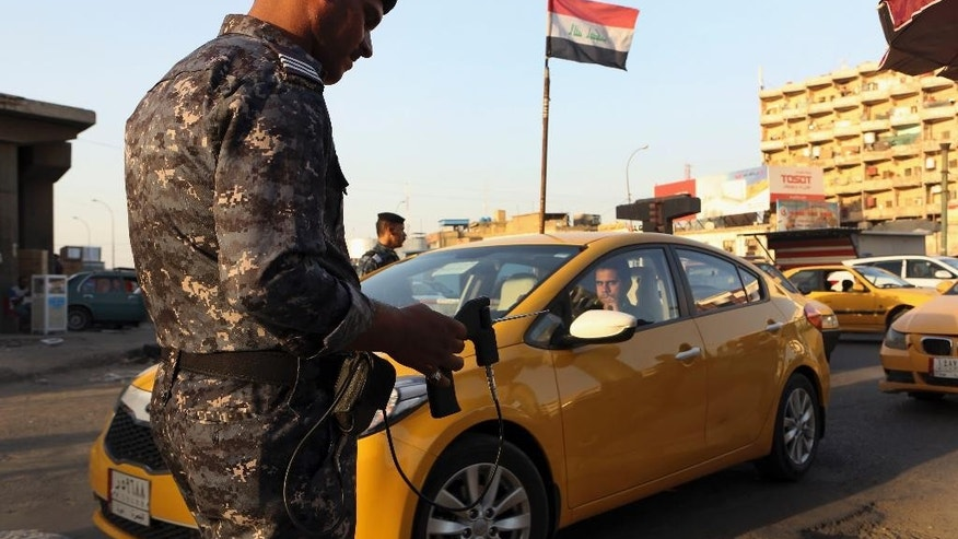 In this Thursday, July 14, 2016 picture, an Iraqi policeman uses a hand-held device that is supposed to detect bombs at a checkpoint in Basra, 340 miles (550 kilometers) southeast of Baghdad, Iraq. For nearly a decade, when you drove through one of Baghdad's seemingly endless checkpoints, a soldier would point a hand-held, gun-shaped device at your vehicle, intently watching if the antenna atop the device moved. If it pointed at your vehicle, the theory was, it had found a possible bomb. The wands were a fake, but it wasn't till a massive bombing this month that the government halted their use.  (AP Photo/Nabil al-Jurani)