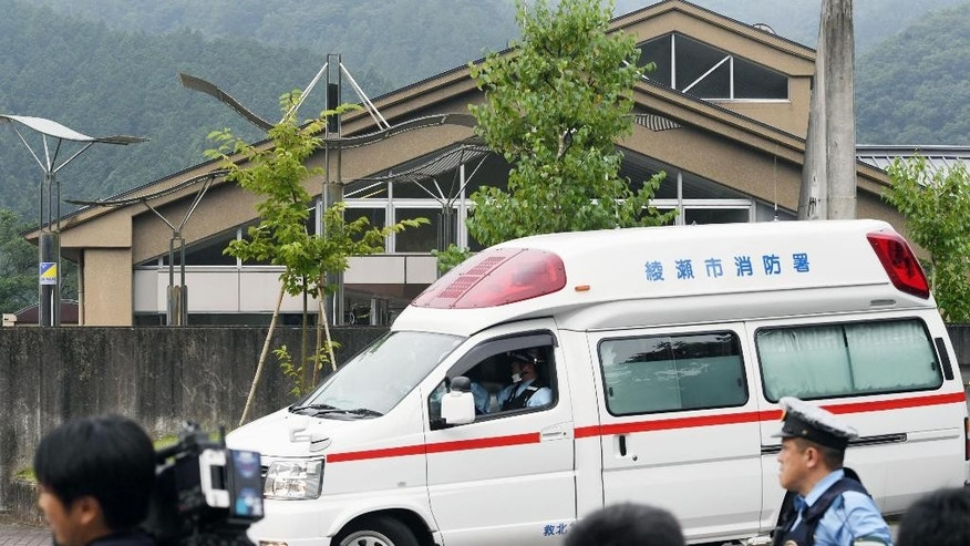 An ambulance moves past in front of a facility for the handicapped where a number of people were killed and dozens injured in a knife attack Tuesday, July 26, 2016,  in Sagamihara, outside Tokyo. (Kyodo News via AP)