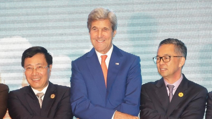 From left, Vietnam Foreign Minister Pham Binh Minh, U.S. Secretary of State John Kerry, and an unidentified delegate from Malaysia, pose for a group photo as they shake hands for a group photo during the Association of Southeast Asian Nations (ASEAN)-U.S. Southeast Asia's main grouping made a last-ditch attempt to reach a consensus on countering China's territorial expansion in the South China Sea, but their deadlock appeared far from being resolved as minutes ticked by before a critical meeting with the Chinese foreign minister Monday. (AP Photo/Sakchai Lalit)