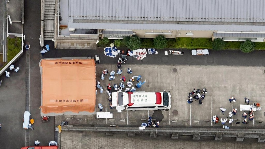 Ambulance crew are seen outside a facility for the handicapped where a number of people were killed and dozens injured in a knife attack Tuesday, July 26, 2016, in Sagamihara, outside Tokyo. (Kyodo News via AP)