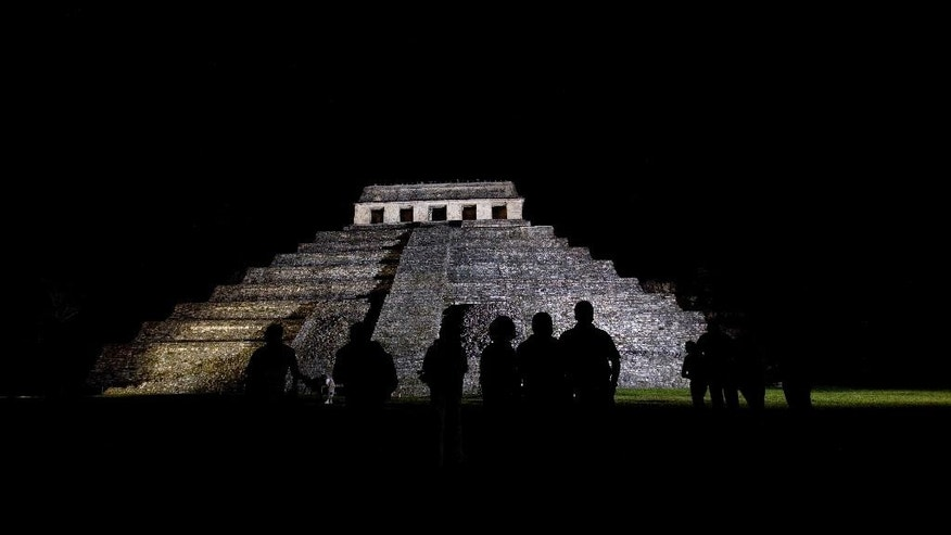 FILE - In this March 10, 2008 file photo, journalists appear silhouetted against a Mayan temple, before covering the meeting of 'Indigenous People to Heal Our Mother Earth'' in Palenque, Mexico.  Archaeologists at Palenque have discovered an underground water tunnel built under the Temple of Inscriptions, which houses the tomb of Mayan ruler Pakal. Archaeologists believe the tunnels were built to give Pakal's spirit a path to the underworld. (AP Photo/Alexandre Meneghini, File)