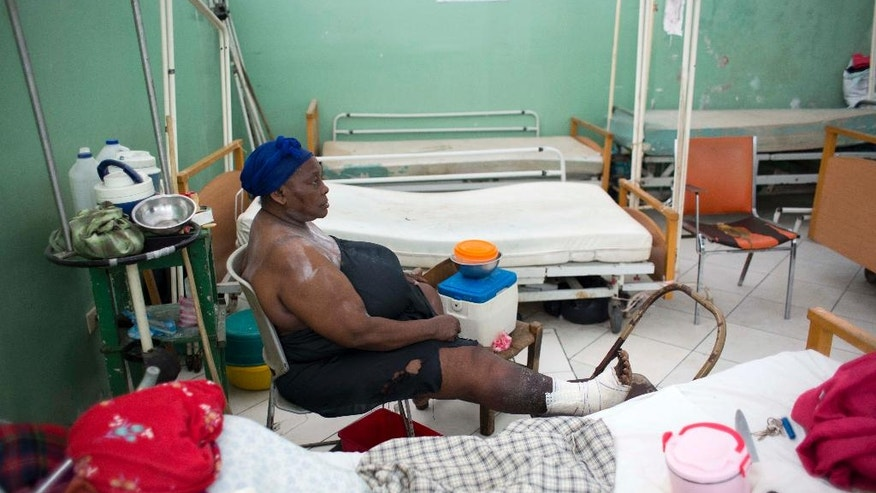 """In this July 19, 2016 photo, patient Penina Pierre sits alone in a dermatology ward, her bandaged foot propped on a chair, at the Hospital of the State University of Haiti, in Port-au-Prince. Across Haiti, a punishing strike by doctors and interns will soon enter its fourth month. Visiting missionaries are keeping her fed since she has no family. """"Maybe someday the doctors will come back,"""" Pierre said. (AP Photo/Dieu Nalio Chery)"""