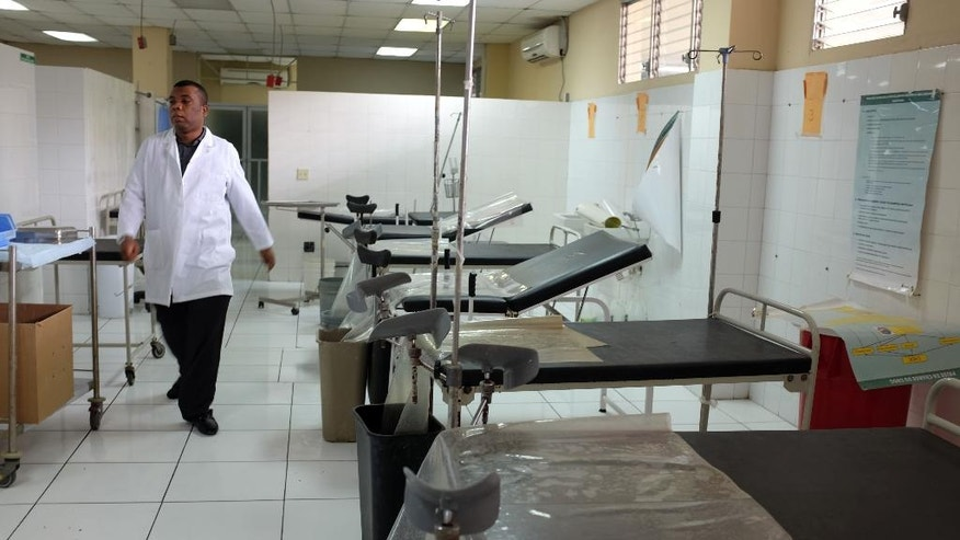In this July 15, 2016 photo, Dr. Joseph Herold walks past a row of gynecological examination tables at La Paix Hospital in Delmas, Haiti. Across the Caribbean country , a punishing strike by doctors and interns will soon enter its fourth month. Since 1996, resident doctors in Haiti have been paid $120 per month, a paltry salary that has been eroded further by the rising cost of living. (AP Photo/Dieu Nalio Chery)
