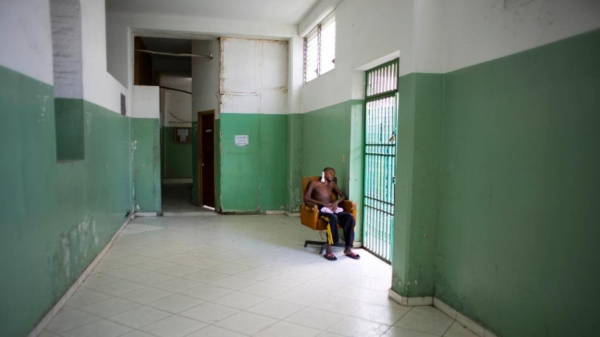 In this July 15, 2016 photo, a young cancer patient sits in a chair waiting for his treatment at the the Hospital of the State University of Haiti, in Port-au-Prince. The country's longest hospital strike comes as a political impasse between feuding factions shows no sign of ending either, leaving the poorest citizens suffering most amid Haiti's latest leadership drift. (AP Photo/Dieu Nalio Chery)