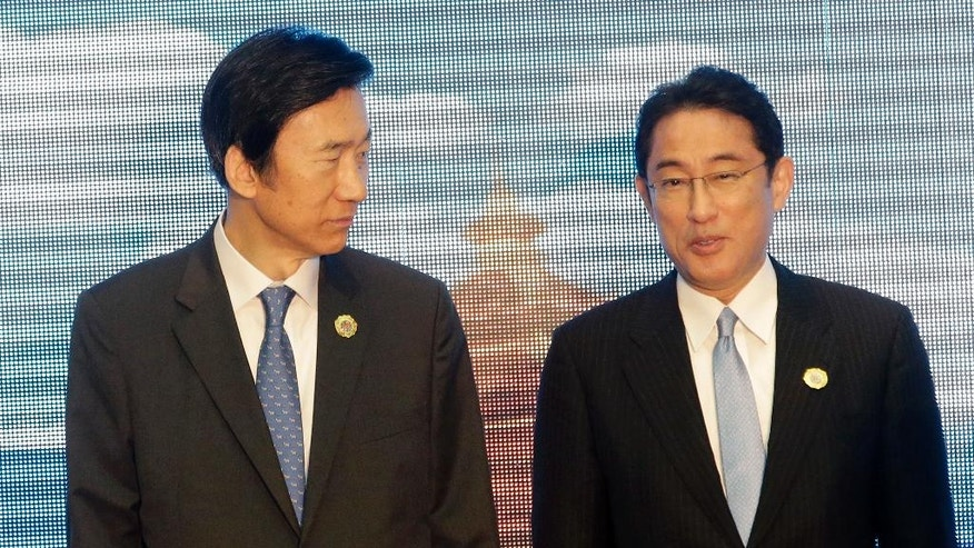 South Korea's Foreign Minister Yun Byung-se, left, talks to Japan's Foreign Minister Fumio Kishida before they pose for a photo during the Association of Southeast Asian Nations (ASEAN) Foreign Ministers' Meeting in Vientiane, Laos, Tuesday, July 26, 2016. (AP Photo/Sakchai Lalit)