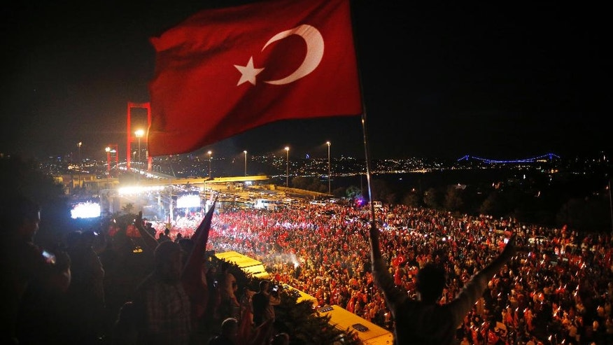 Pro-government supporters protest on the road leading to Istanbul's iconic Bosporus Bridge,background left, Thursday, July 21, 2016. Turkish lawmakers convened to endorse sweeping new powers for Turkey's President Recep Tayyip Erdogan that would allow him to expand a crackdown in the wake of July 15 failed coup. The 550-member parliament is set to approve Erdogan's request for a three-month state of emergency. (AP Photo/Emrah Gurel)