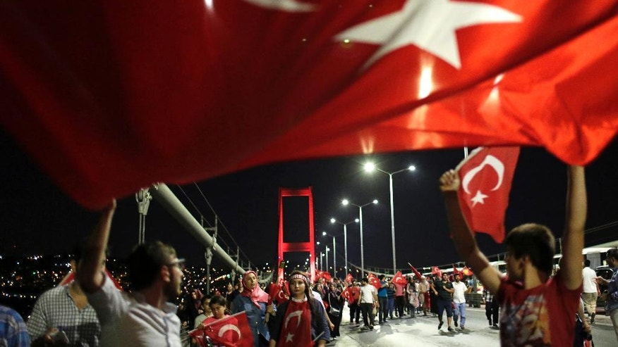 Pro-government supporters wave a Turkish flag as they protest on Istanbul's iconic Bosporus Bridge, late Thursday, July 21, 2016. Turkish lawmakers approved a three-month state of emergency, endorsing new powers for Turkey's President Recep Tayyip Erdogan that would allow him to expand a crackdown that has already included mass arrests and the closure of hundreds of schools, in the wake of the July 15 failed coup. (AP Photo/Petros Giannakouris)