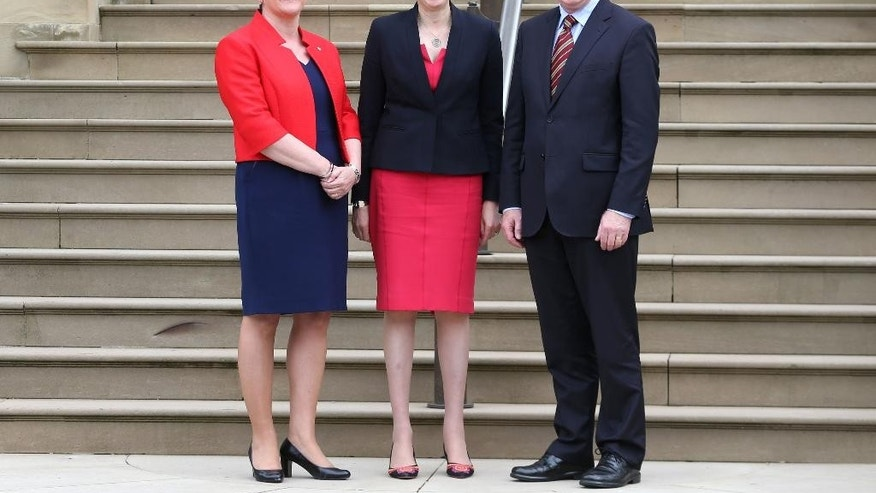 Britain's Prime Minister Theresa May, centre,  is greeted by Northern Ireland's First Minister Arlene Foster, left and Deputy First Minister Martin McGuinness upon arrival at Stormont Castle in Belfast, Northern Ireland, Monday July 25, 2016. May met Northern Ireland's leaders in Belfast Monday in a bid to allay Northern Irish concerns about Britain's vote to leave the European Union. (Liam McBurney/PA via AP)