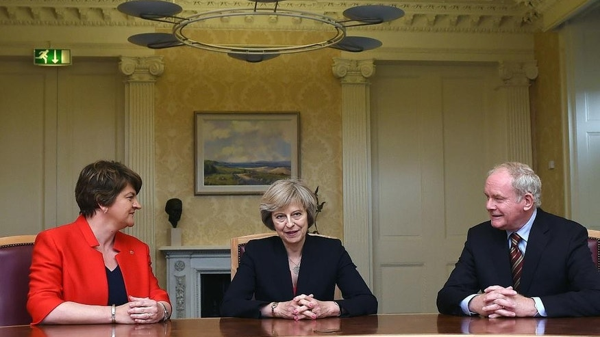 Britain's Prime Minister Theresa May, centre, poses for a photo with Northern Ireland's First Minister Arlene Foster, left and Deputy First Minister Martin McGuinness, prior to their meeting, Stormont Castle in Belfast, Northern Ireland, Monday July 25, 2016. May met Northern Ireland's leaders in Belfast Monday in a bid to allay Northern Irish concerns about Britain's vote to leave the European Union. (Charles McQuillan/PA via AP)