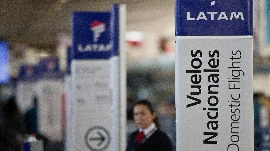 An agent of LATAM airlines stands by the counters at the airport in Santiago, Chile, Monday, July 25, 2016. LATAM airlines created in 2012 after a fusion between the airlines LAN of Chile and TAM of Brazil, has agreed to pay more than $22 million in fines related with a scheme to bribe Argentine union officials via a false consulting contract. The airline will pay the fine to the Securities and Exchange Commission (SEC) and the Department of Justice (DOJ) for a violation of the accounting provisions of the Foreign Corrupt Practices Act. (AP Photo/Esteban Felix)