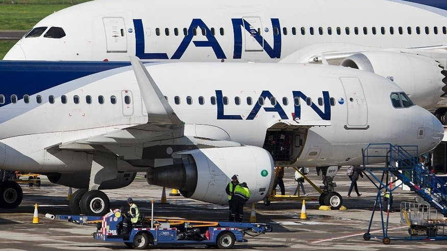 Two LAN jet liners sit parked on the tarmac at the airport in Santiago, Chile, Monday, July 25, 2016. LATAM airlines created in 2012 after a fusion between the airlines LAN of Chile and TAM of Brazil, has agreed to pay more than $22 million in fines related with a scheme to bribe Argentine union officials via a false consulting contract. The airline will pay the fine to the Securities and Exchange Commission (SEC) and the Department of Justice (DOJ) for a violation of the accounting provisions of the Foreign Corrupt Practices Act. (AP Photo/Esteban Felix)