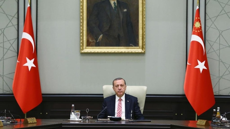 Under a portrait of Turkish Republic founder Mustafa Kemal Ataturk,Turkey's President Recep Tayyip Erdogan chairs the cabinet meeting, in Ankara, Turkey, Monday, July 25, 2016. Turkey on Monday issued warrants for the detention of 42 journalists suspected of links to the alleged organizers of a failed military uprising, intensifying concerns that a sweeping crackdown on alleged coup plotters could target media for any news coverage critical of the government. (Presidential Press Service, Pool via AP)